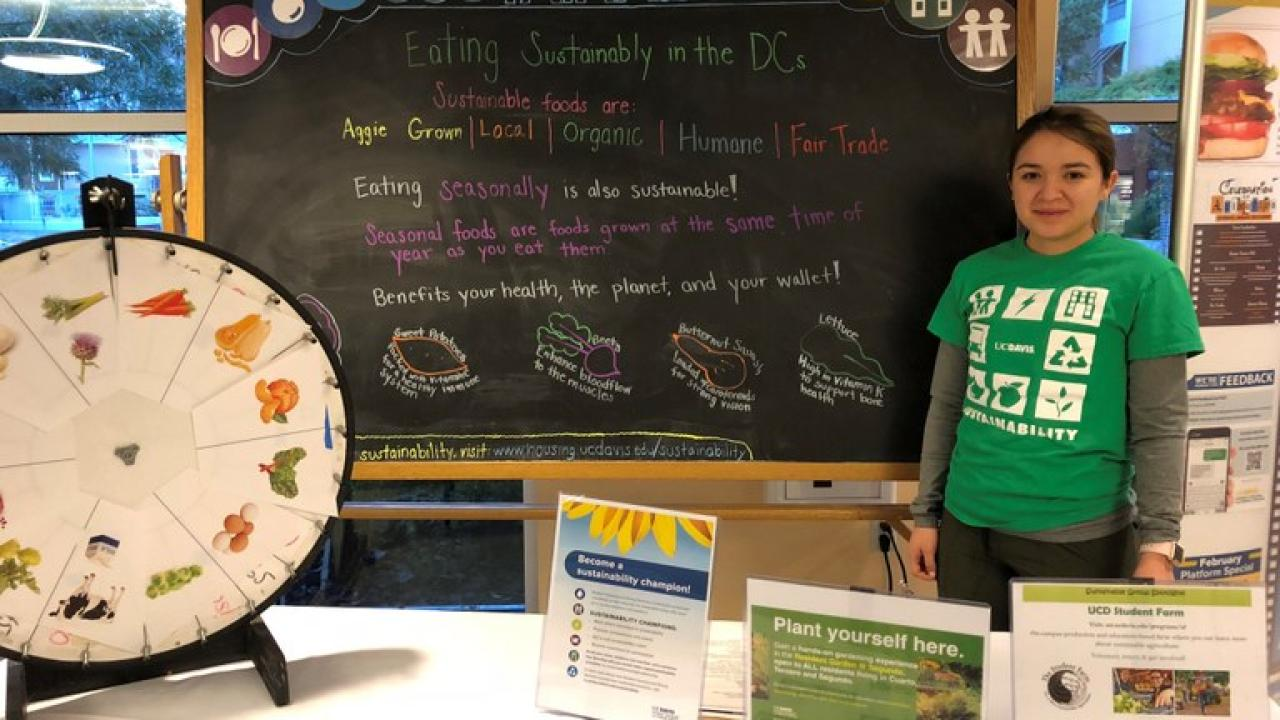 UC Davis Dining Sustainability Intern tabling on the topic of sustainable food options, highlighting sustainable food menu icon definitions, such as Aggie Grown and Local. Photo Credit Skylar Johnson, Student Housing and Dining Services.