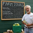 man standing in front of farm tours sign